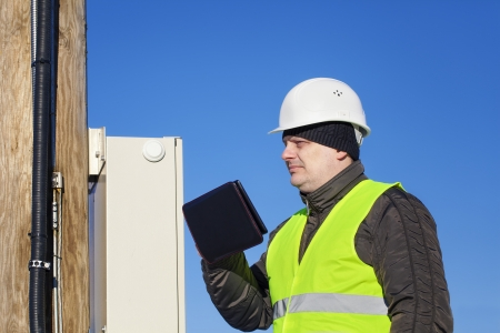 isolators: Electrician with tablet PC inspect electric lines Stock Photo
