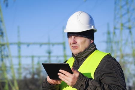Electrician with tablet PC inspect electric lines technical quality