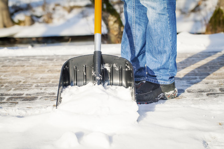 Man with a snow shovel on the sidewalk