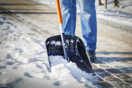 clima: Hombre con pala de nieve limpia las aceras en invierno