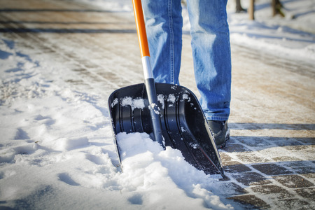 Man met sneeuw shovel reinigt trottoirs in de winter