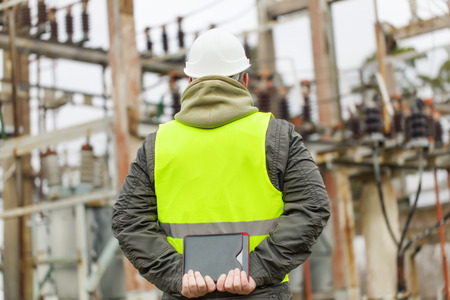 isolators: Electrical Engineer with tablet PC in electrical substation