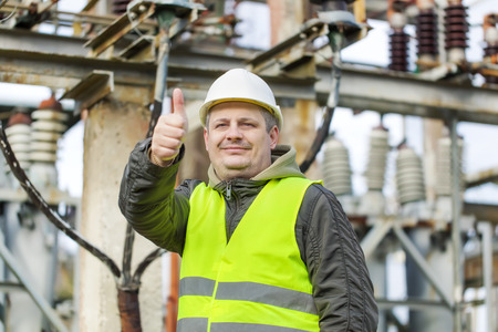 isolators: Electrician in electrical substation near to high-voltage cable