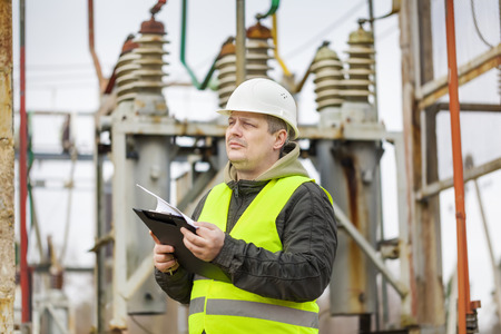 Electrical Engineer with folder in electrical substation