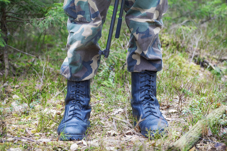 Soldier s legs in army boots in a forest photo
