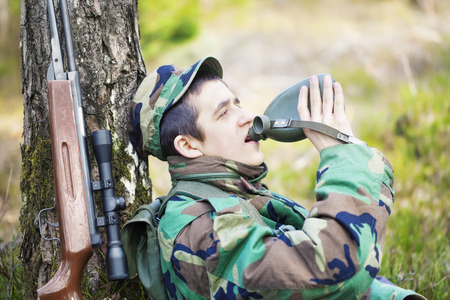recruit: Recruit with water bottle in forest near tree