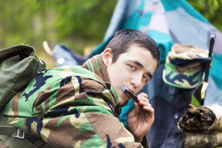 recruit: Young recruit with harmonica and rifle in forest