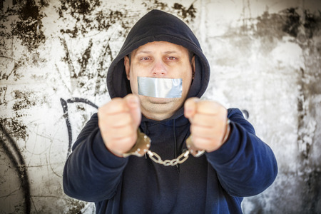 Hostage in handcuffs with tape on the mouth photo