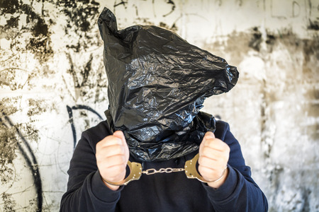 Hostage in handcuffs and with a bag on head photo