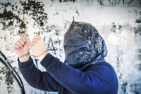 Hostage in handcuffs and with a bag on head near wall photo