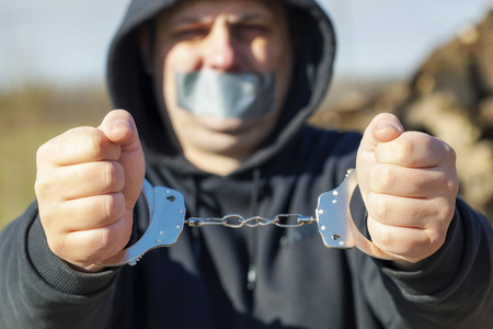 Hostage in handcuffs at outdoor photo