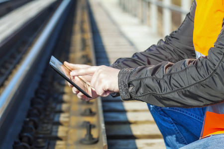 Railroad worker with tablet PC near railway Фото со стока