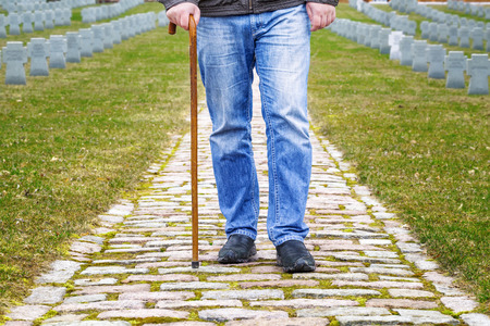 Man with walking stick in cemetery