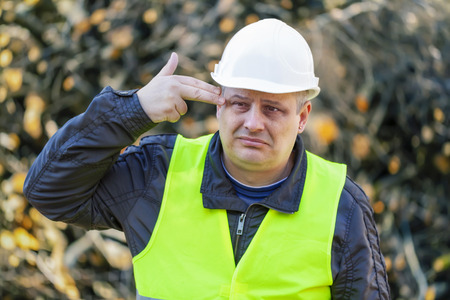 Worried lumberjack in forest near the branch pile Stock Photo