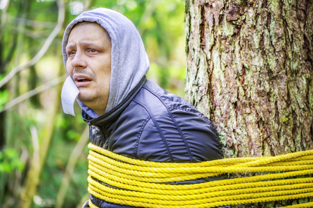 Man tied to a tree in the forest photo