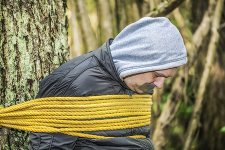 Man with tape on mouth tied to the tree in the forest photo