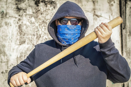 Man with a baseball bat on old wall background Stockfoto