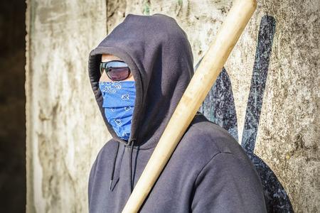 vandal: Man with a baseball bat at old wall background