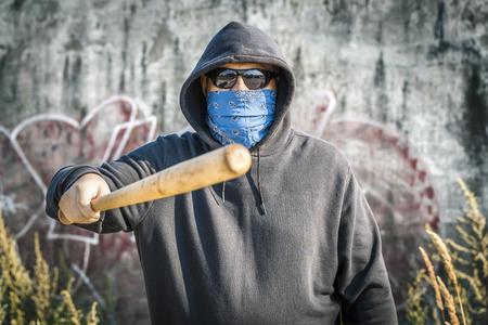 Man holds a baseball bat forward on a wall background Stockfoto