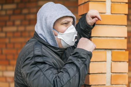 Man in the air mask at the brick wall