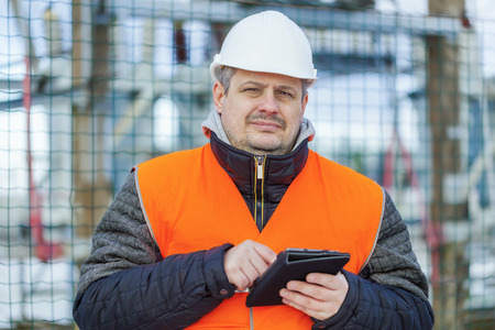isolators: Electrical Engineer with tablet PC near the electric substation
