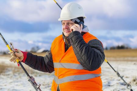 ingenieur electricien: Ing�nieur �lectrique parlant au t�l�phone cellulaire � proximit� tendeur