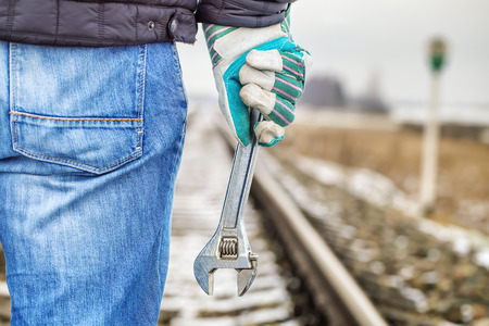 Man with adjustable wrench on the railroad photo