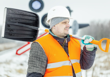Worker with snow shovel near signal beacons in winter