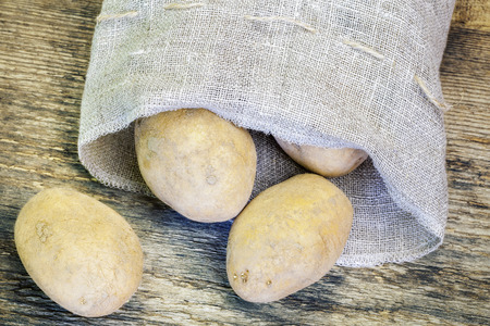 linen bag: Potatoes in linen bag on the wooden table
