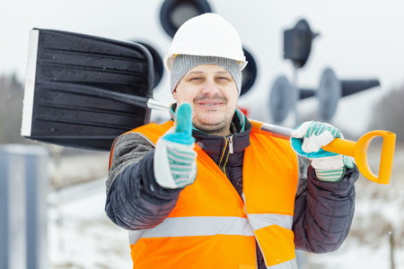 Worker with snow shovel near signal beacons in snowy day