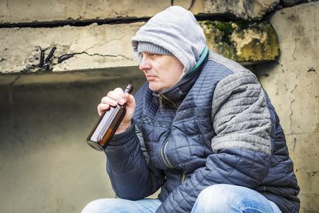 sorrowful: Sorrowful man with beer bottle on the bridge Stock Photo