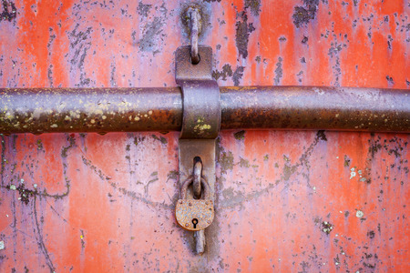 Old rusted padlock on red metal door photo