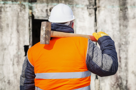 Worker with sledge hammer against the wall Stockfoto