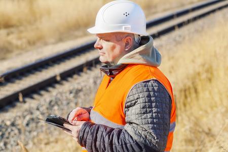 Railway Engineer with tablet PC near to railway