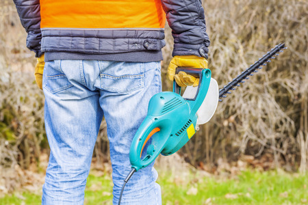 cut off saw: Landscape worker with bush cutter near bush in spring Stock Photo