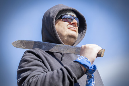 outrage: Man with machete on shoulder Stock Photo