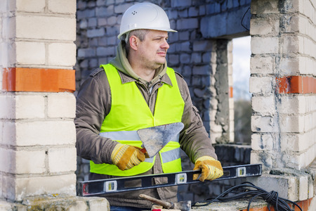construction level: Construction worker with trowel and level near wall Stock Photo