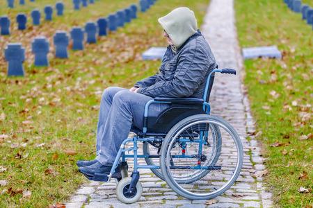 silla de ruedas: Veterano discapacitado en silla de ruedas en el cementerio