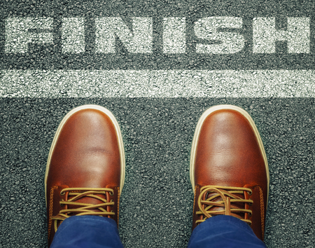 end of the line: Man before inscription Finish on asphalt Stock Photo