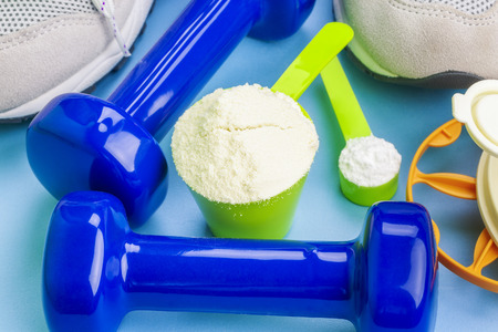 whey: Scoops with pure whey protein and creatine with sport items around