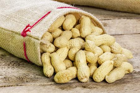 cacahuate: Cacahuetes con c�scara en la bolsa de tejido de yute Foto de archivo