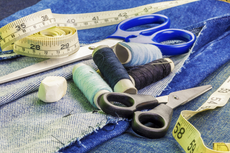 modiste: Threads with needles, scissors, and tape measure on denim fabric