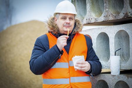 Arbeiter essen französisch frites auf der Baustelle Standard-Bild - 56182883