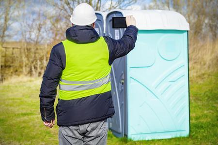 latrine: Inspector filmed on the tablet PC near portable toilets Stock Photo