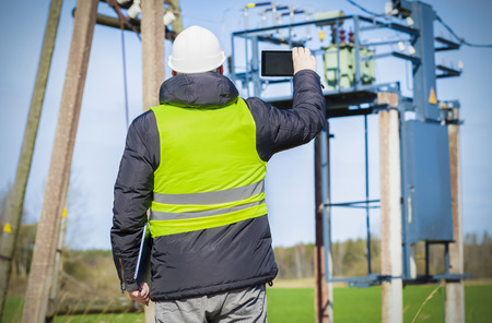 power transformer: Engineer take pictures on tablet PC near power transformer