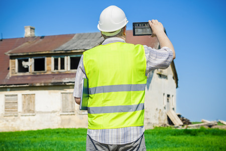 damaged house: Building inspector filming on tablet PC near old abandoned, damaged house on grass field