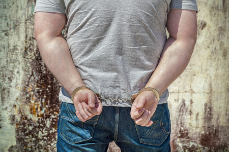 enslaved: Man locked in handcuffs near wall Stock Photo