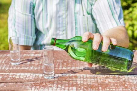 the drinker: Man poured glass of alcohol