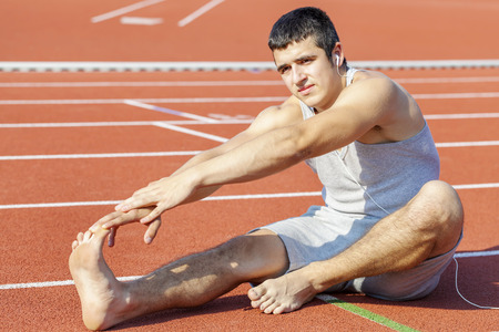 sweatsuit: Young athlete stretching on stadium Stock Photo