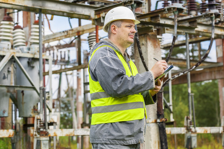 electricity company: Electrician writing in electrical substation